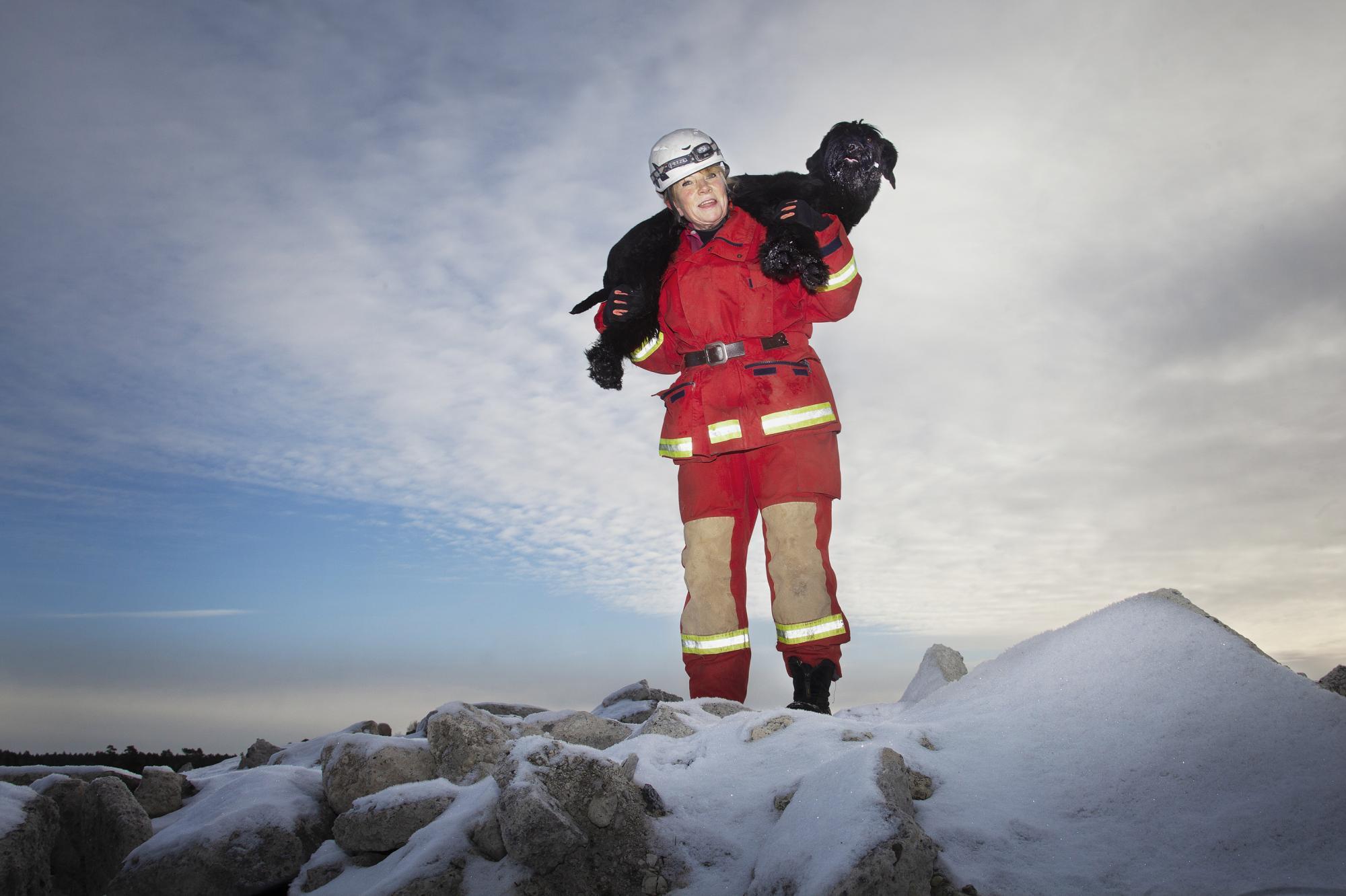 En räddningshund måste acceptera att bli buren och för att orka bära Putte en längre sträcka är han tränad att ligga på hennes axlar.