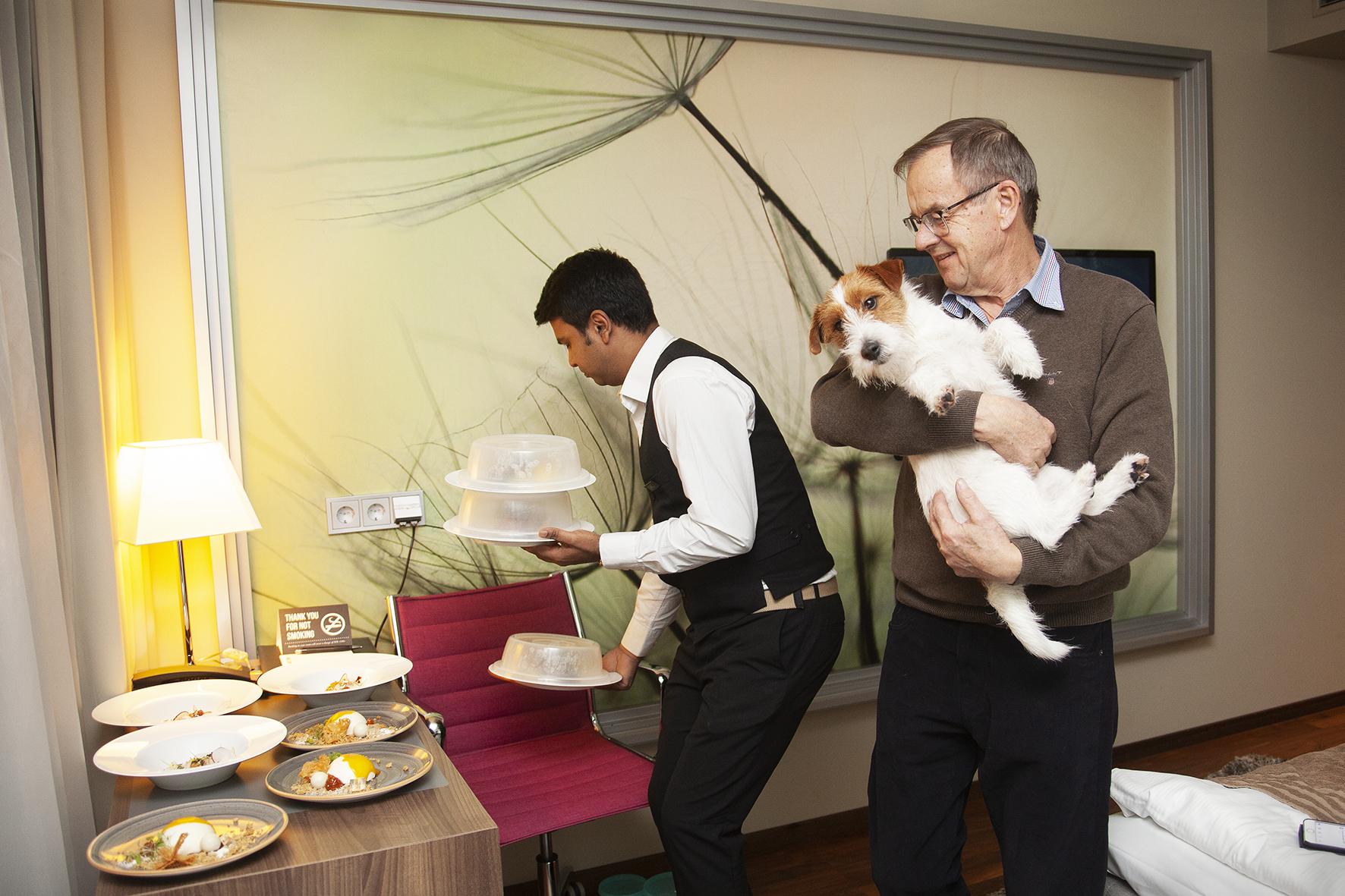 <span>Lennart Stensved tar hand om Jack Russellhannen Sigge medan nyårssupén anländer till rummet.</span>